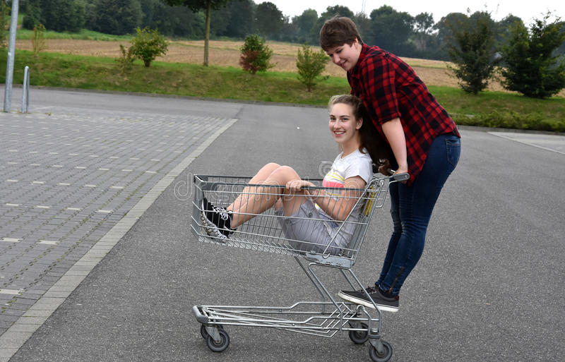 Teenage girlfriends with shopping cart royalty free stock images