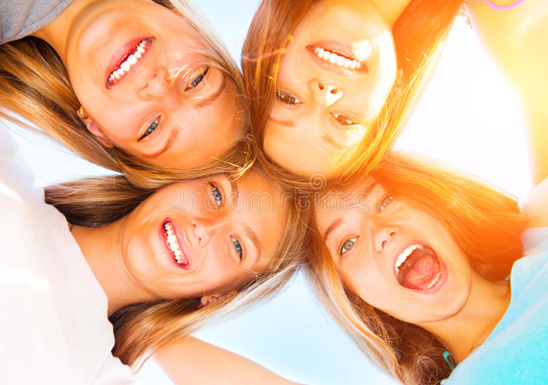Teenage girlfriends staying together over blue sky. Girlfriends staying together, looking at camera and laughing over blue sky royalty free stock image