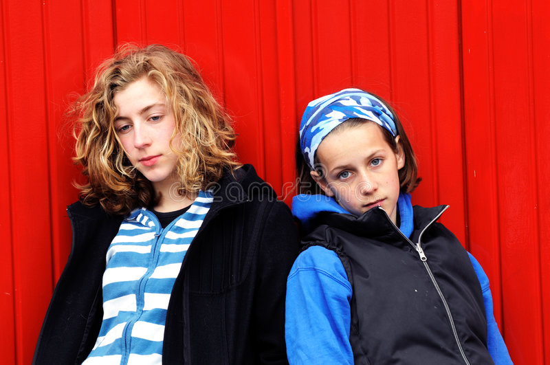 Teenage girls against red wall royalty free stock photos