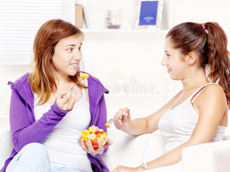 Teenage girls chating and eating fruit salad royalty free stock images