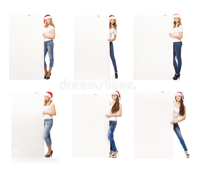 Teenage girls in Christmas hats holding white banners stock images