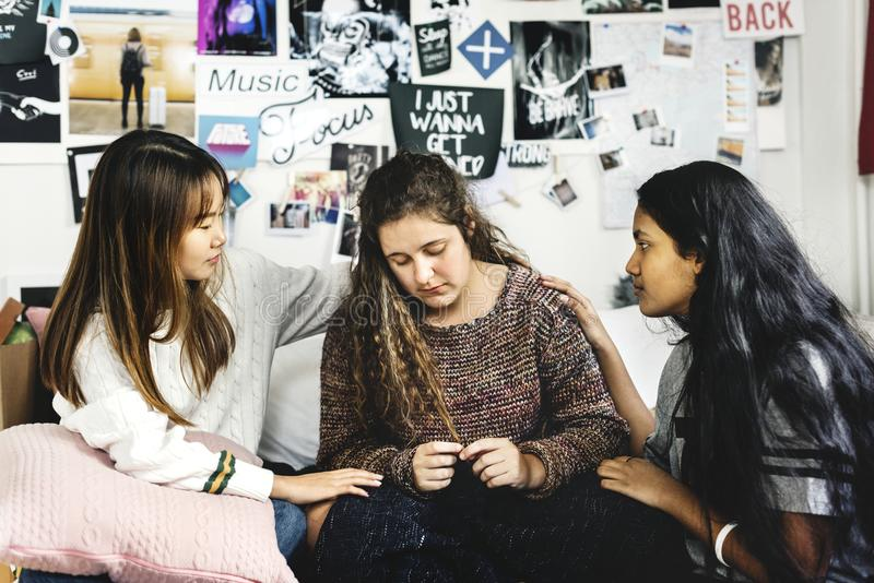 Teenage girls consoling their depressed crying troubled friend royalty free stock photography