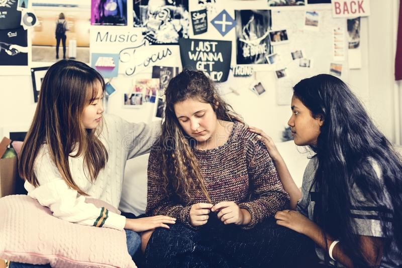 Teenage girls consoling their depressed crying troubled friend royalty free stock photo