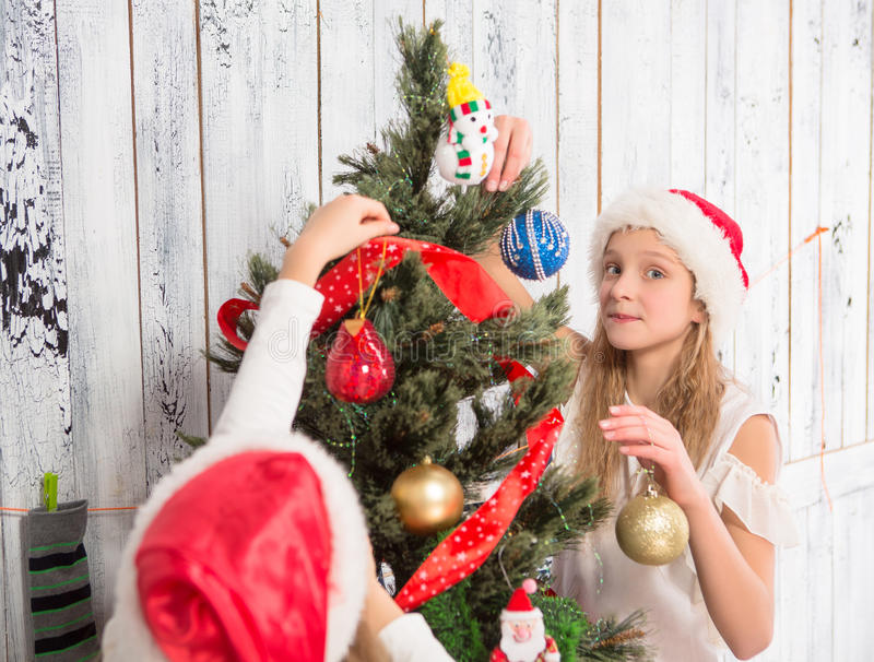 Teenage girls decorating New Year tree at home stock images