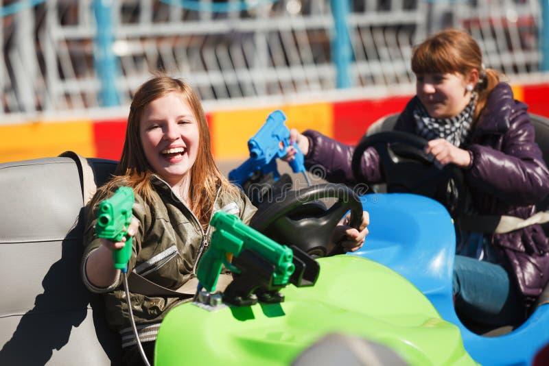 Teenage girls driving a bumper cars stock image