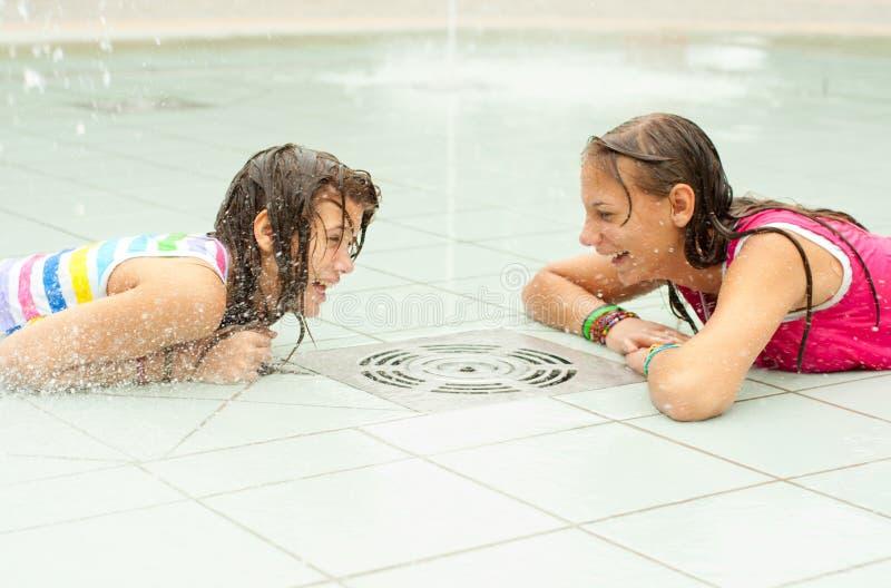 Teenage girls having fun in the towns fountain royalty free stock image