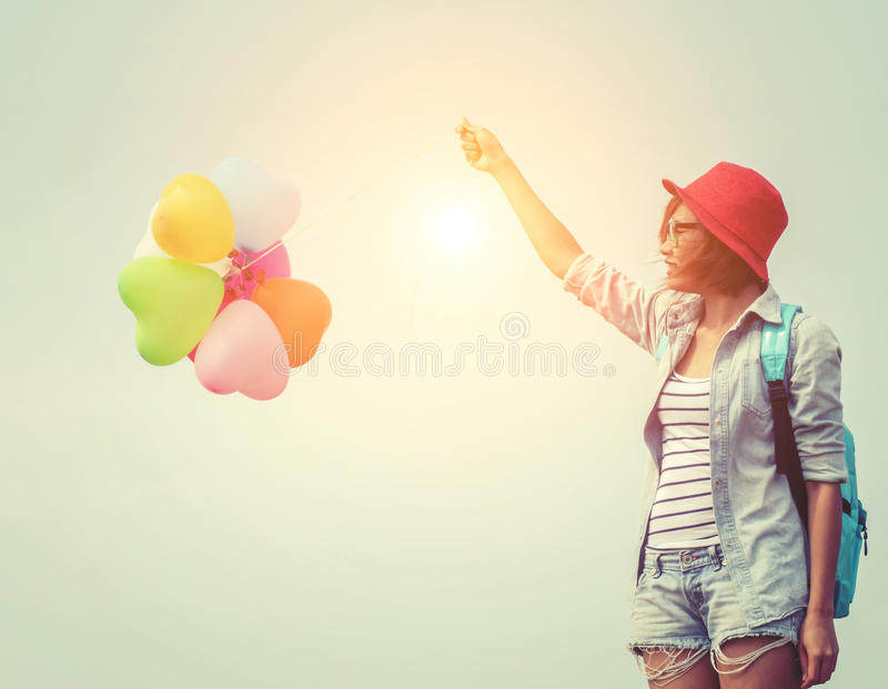 Teenage girls holding colorful balloons. carrying Blue backpack stock photos