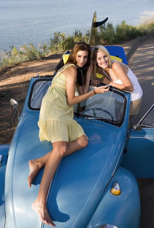 Teenage girls (17-19) listening to MP3 player on car bonnet, sharing headphones, elevated view stock images