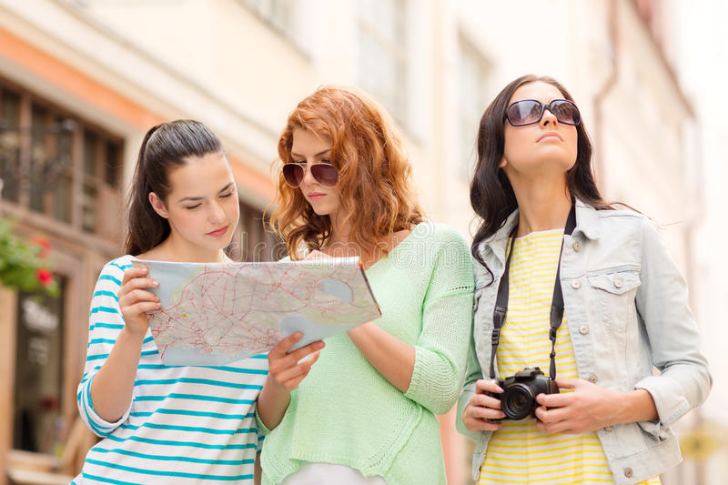 Teenage girls with map and camera royalty free stock photos