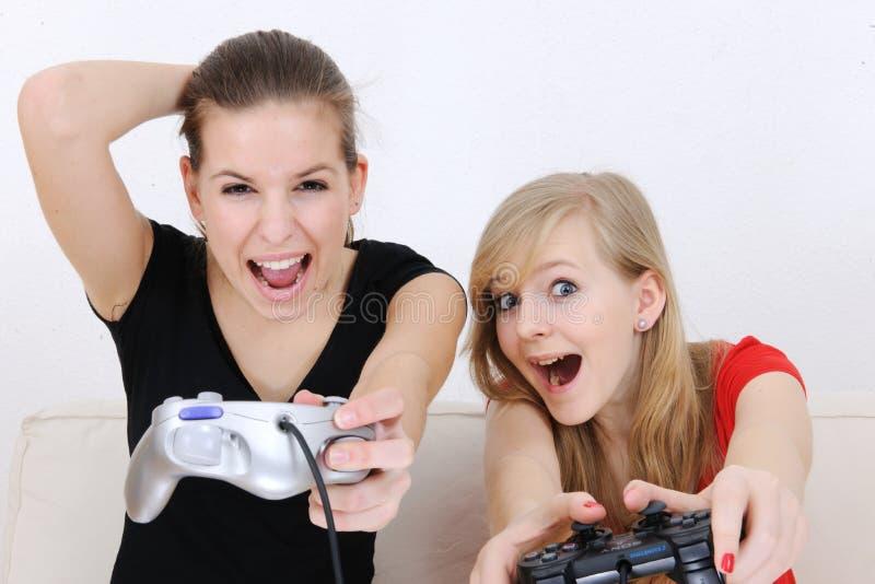 Teenage girls playing playstation stock photos
