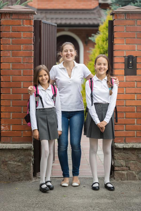 Two teenage girls posing with mother in front of big house before going to school stock photo