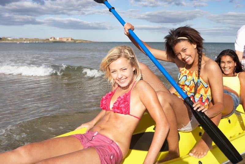Teenage girls in sea with canoe royalty free stock image