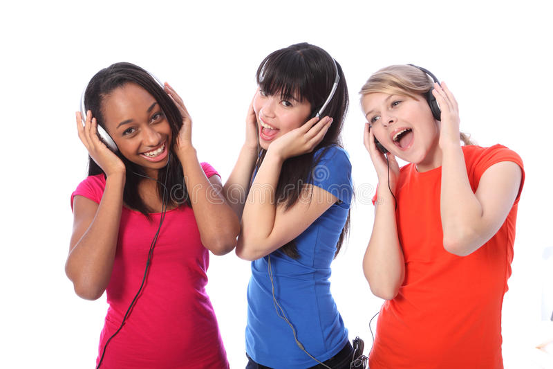 Teenage girls singing to music on mobile phones. Three beautiful young teenager girl friends a blonde caucasian, an oriental Japanese and an African American royalty free stock photos