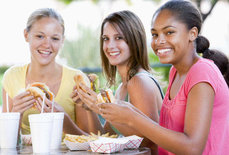 Teenage Girls Sitting Outdoors Eating Fast Food. Smiling royalty free stock images