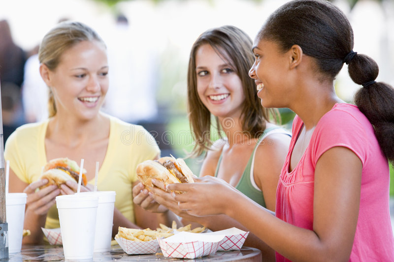 Teenage Girls Sitting Outdoors Eating Fast Food. Smiling stock photography