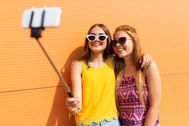 Teenage girls taking picture by selfie stick. Fashion, leisure and people concept - smiling teenage girls taking picture by smartphone on selfie stick outdoors stock photo