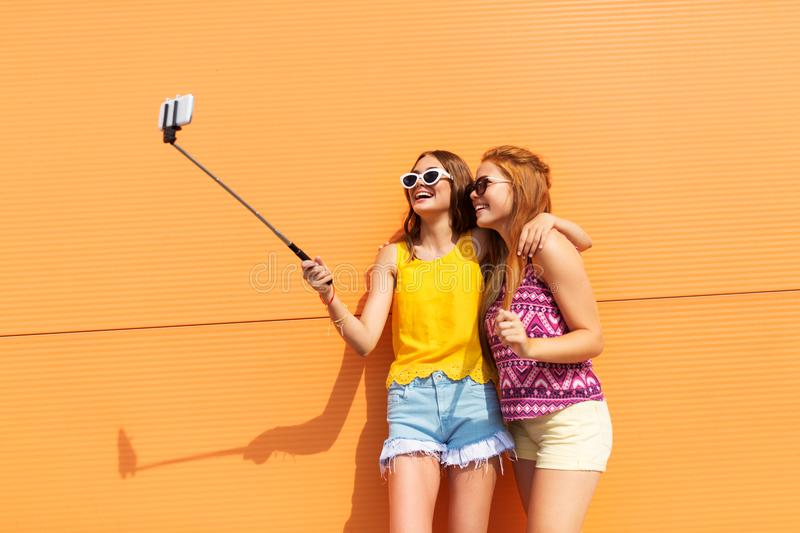 Teenage girls taking picture by selfie stick. Fashion, leisure and technology concept - smiling teenage girls taking picture by smartphone on selfie stick royalty free stock photo