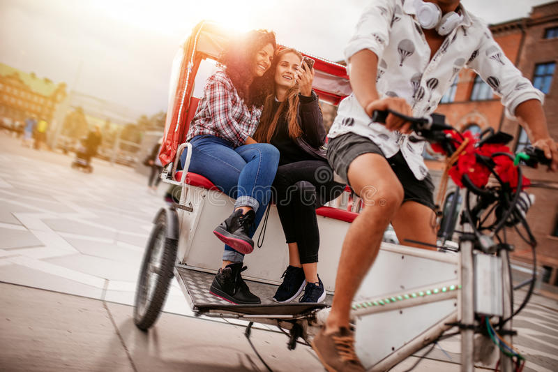 Teenage girls taking selfie on tricycle ride stock images