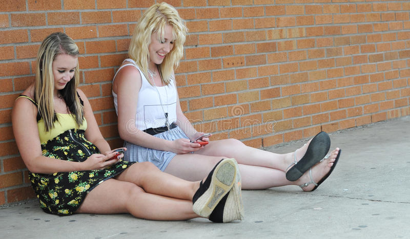 Teenage girls texting with mobile stock image
