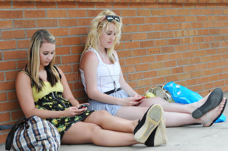 Teenage girls texting with mobile cellphones royalty free stock photography