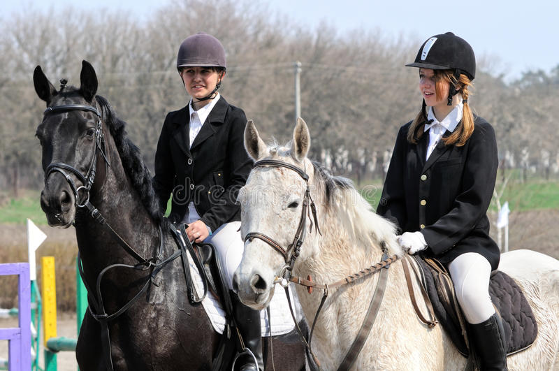 Teenage girls and tired horses. After the jumping show stock photo