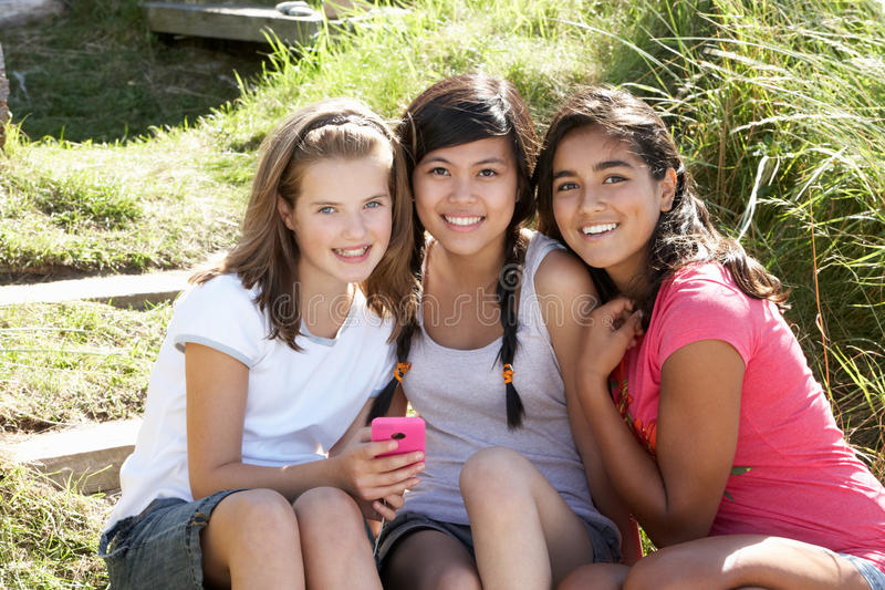 Teenage girls using phone outdoors stock photo