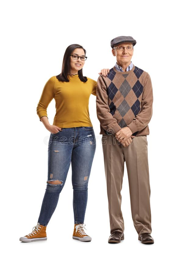 Teenage granddaughter and grandfather posing stock photo