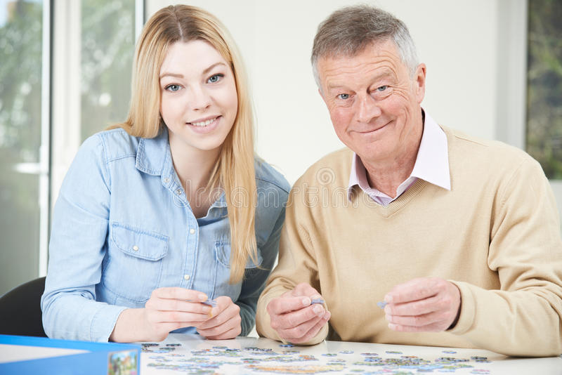 Teenage Granddaughter Helping Grandfather With Jigsaw Puzzle royalty free stock photo