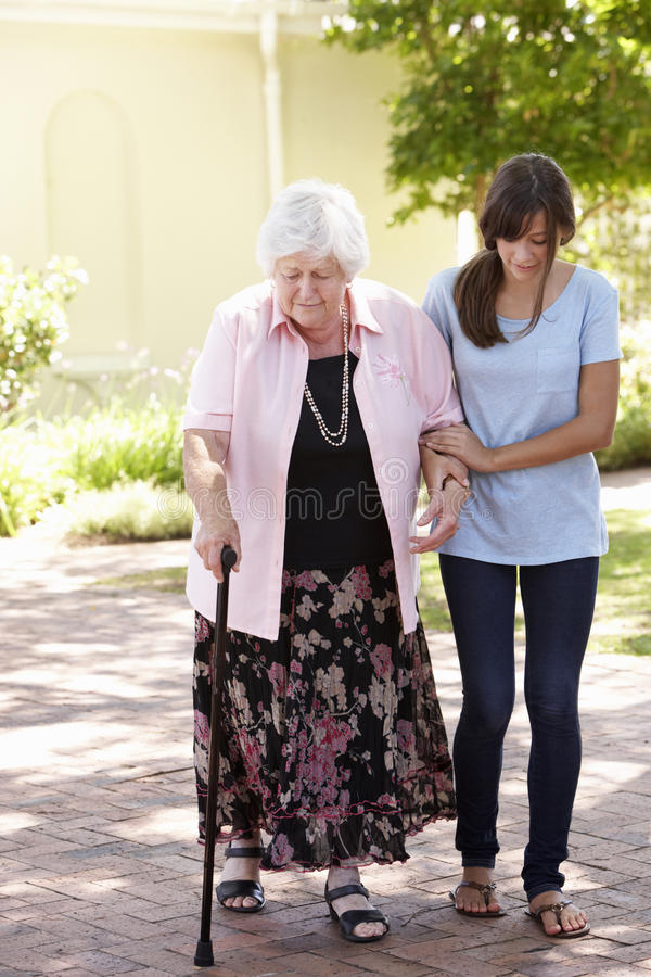 Teenage Granddaughter Helping Grandmother Out On Walk royalty free stock image