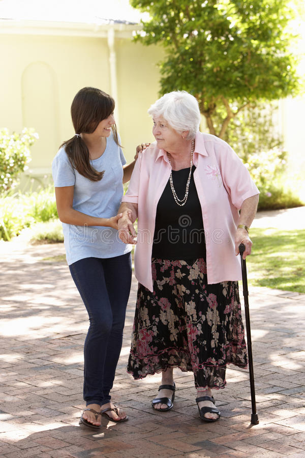 Teenage Granddaughter Helping Grandmother Out On Walk stock image