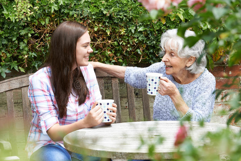 Teenage Granddaughter Relaxing With Grandmother In Garden. Teenage Granddaughter With Grandmother In Garden stock images