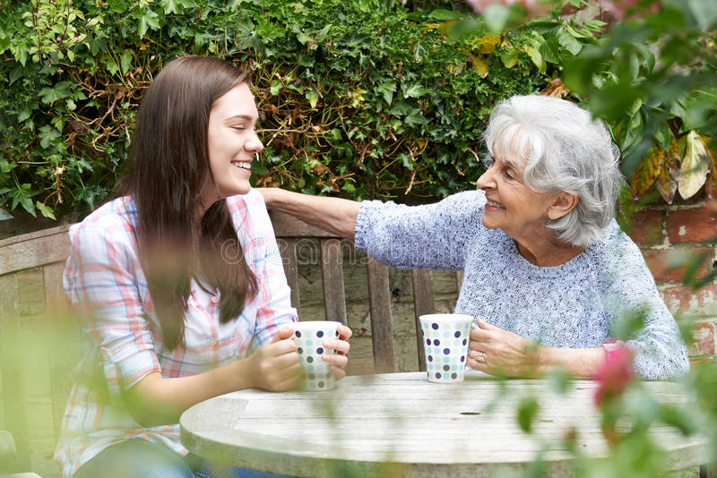 Teenage Granddaughter Relaxing With Grandmother In Garden royalty free stock images