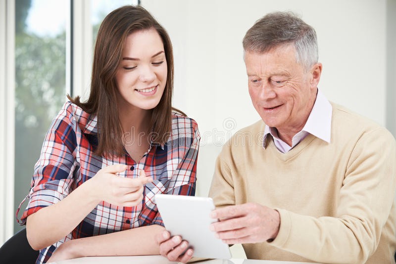 Teenage Granddaughter Showing Grandfather How To Use Digital Tab stock photography