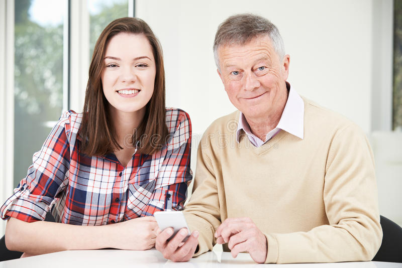 Teenage Granddaughter Showing Grandfather How To Use Mobile Phone stock photography
