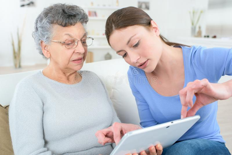 Teenage granddaughter showing grandmother how to use digital tablet royalty free stock photo