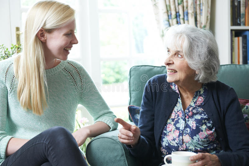 Teenage Granddaughter Visiting Grandmother royalty free stock image
