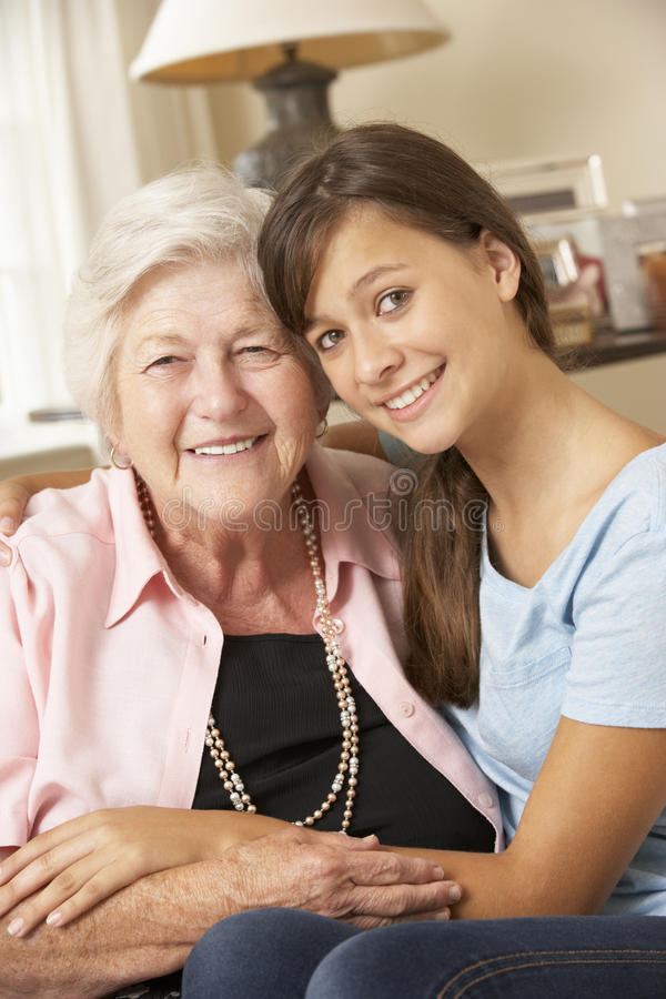 Teenage Granddaughter Visiting Grandmother At Home royalty free stock image