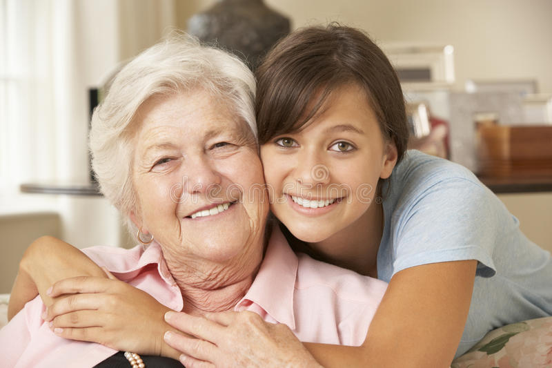 Teenage Granddaughter Visiting Grandmother At Home stock photography