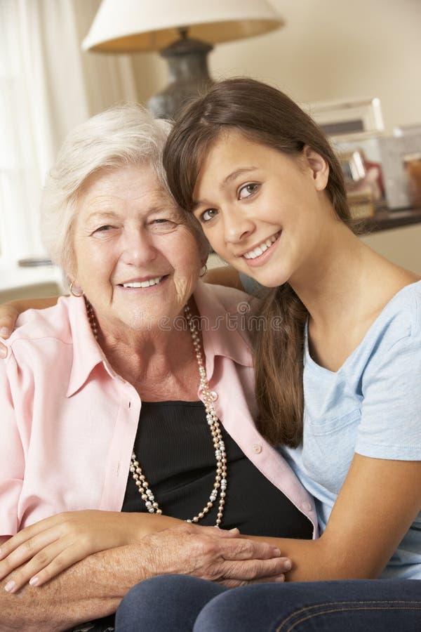Teenage Granddaughter Visiting Grandmother At Home royalty free stock images