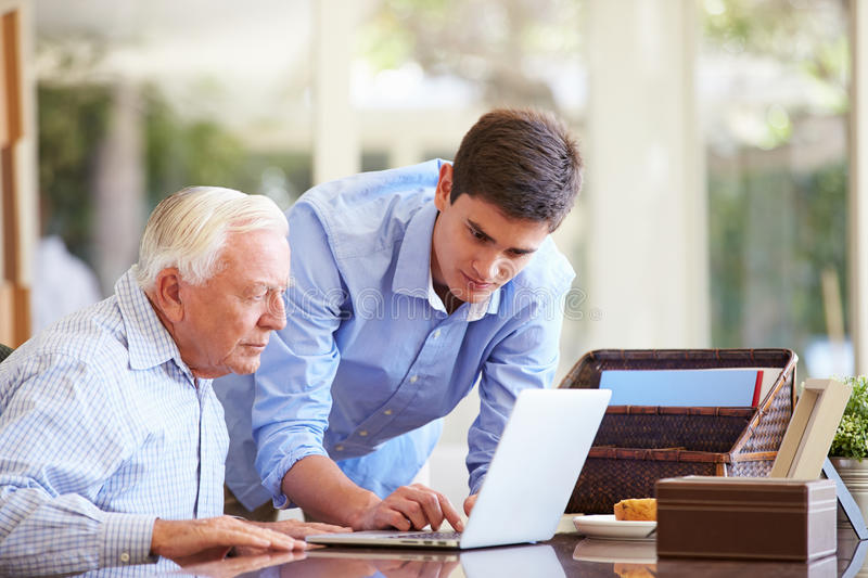 Teenage Grandson Helping Grandfather With Laptop. Looking At Screen stock photos