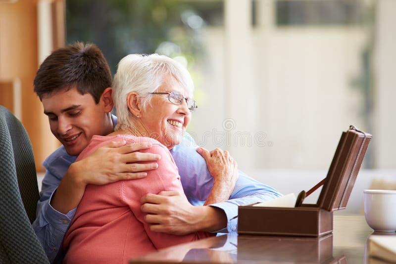 Teenage Grandson Hugging Grandmother. At Home Smiling stock images