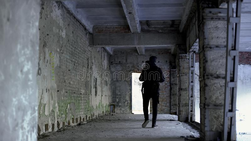 Teenage guy walking in dangerous place, abandoned house, risk of kidnapping. Stock photo stock photos
