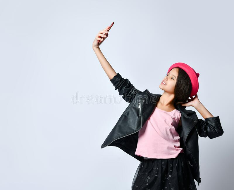 Teenage kid in black leather jacket, skirt and pink hat. She taking selfie using smartphone, posing isolated on white. Close up. Brunette teenage kid in black royalty free stock images