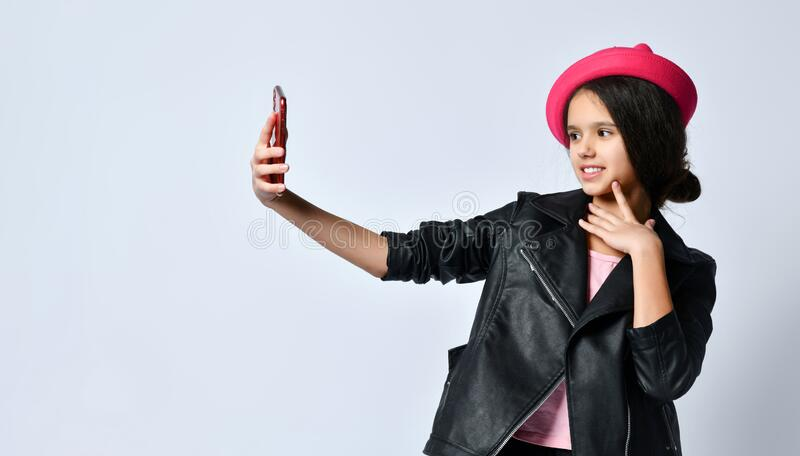Teenage kid in black leather jacket, skirt and pink hat. She taking selfie using smartphone, posing isolated on white. Close up. Brunette teenage kid in black stock photography
