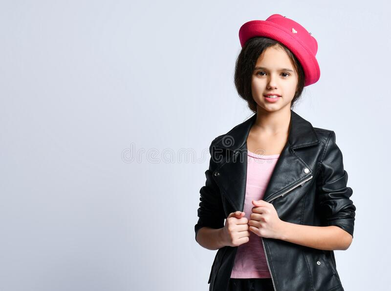 Teenage kid in black leather jacket, skirt, t-shirt, pink hat and sneakers. She smiling, standing isolated on white. Portrait Brunette teenage kid in black stock photography