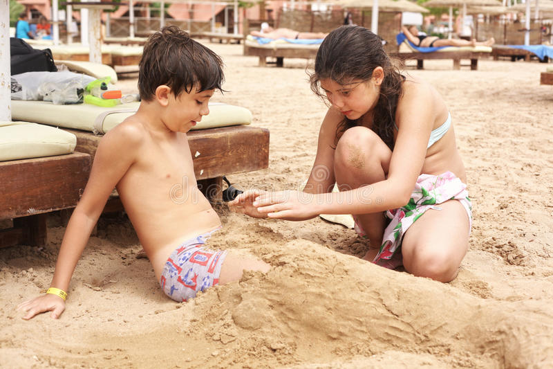 Teenage kids sister and brother play with sand. On tropical beach close up photo stock images