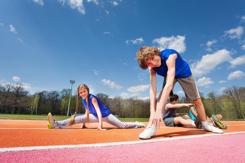 Teenage kids stretching before exercises. On stadium's track on sunny spring day royalty free stock photography