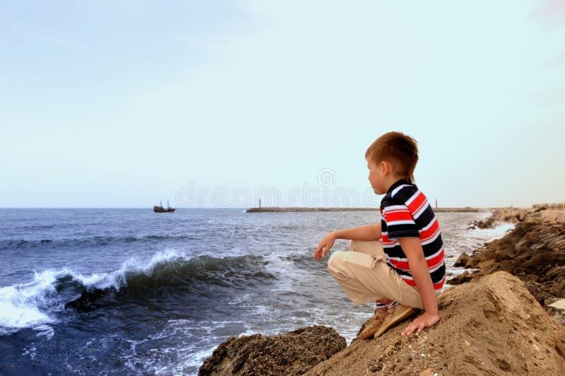 Teenage lookeing faraway on coast of the sea stock photo