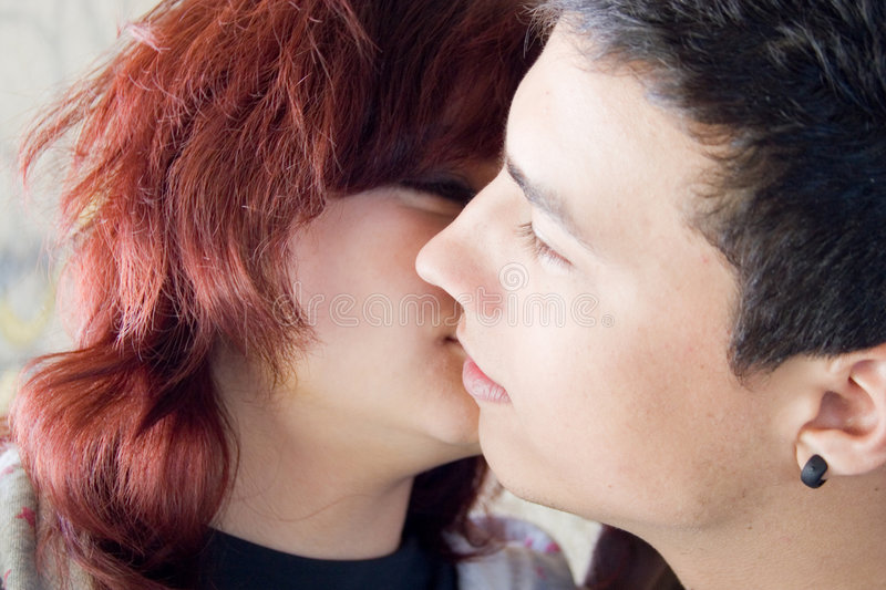 Teenage love. Teenage couple kissing in the street royalty free stock images
