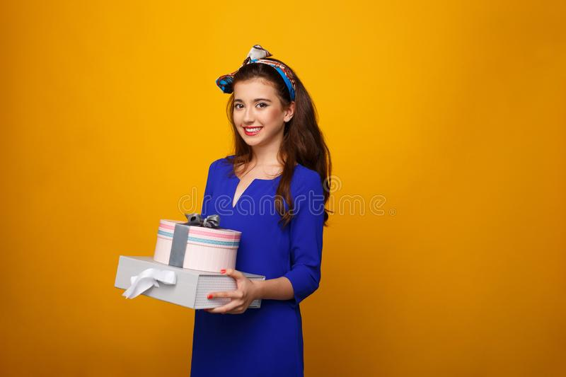 Smiling girl with long curly hair and make up holding in hands gift boxes, over yellow background. Copy space. stock photography